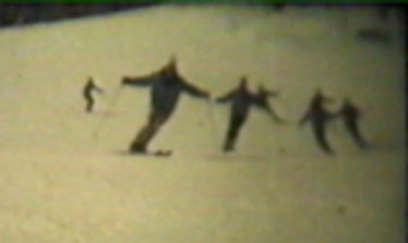 Grainy frame, from an old 16mm film reel, of Walter leading a group of instructors down the Open Slope